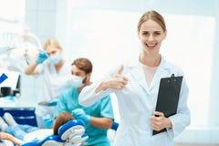 摆在反对对待女孩` s牙牙医的背景的护士  它显示赞许 免版税图库摄影