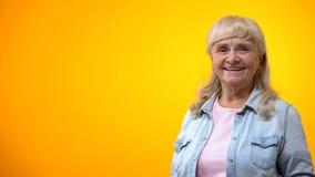 摆在反对明亮的背景,积极态度的微笑的老妇人对生活 免版税库存照片