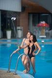 摆在反对游泳池用完善的水色水和做selfie照片用selfie棍子的两个美丽的女孩 免版税图库摄影