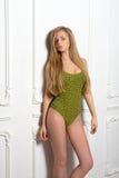 摆在反对的泳装的性感的年轻白肤金发的妇女 免版税库存照片