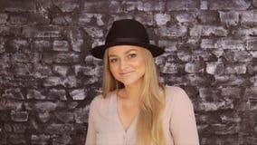 摆在反对砖墙背景的黑帽会议和一件灰色衬衣的一个女孩 影视素材