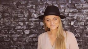 摆在反对砖墙背景的黑帽会议和一件灰色衬衣的一个女孩 股票录像