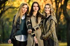 摆在反对秋天的背景的三个时装模特儿停放 库存图片