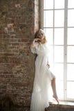 摆在反对窗口的美丽的白色礼服的新娘 库存照片