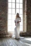 摆在反对窗口的美丽的白色礼服的新娘 库存图片
