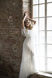 摆在反对窗口的美丽的白色礼服的新娘 免版税库存图片