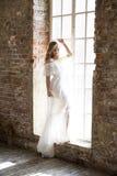 摆在反对窗口的美丽的白色礼服的新娘 图库摄影