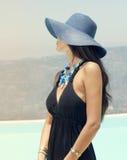 摆在反对蓝天的一个美丽的迷人的女孩的画象在夏时 免版税库存照片