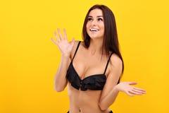 摆在反对黄色背景的比基尼泳装的性感的妇女 库存照片
