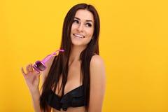 摆在反对黄色背景的比基尼泳装的性感的妇女 免版税库存图片