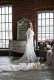 摆在反射在葡萄酒镜子的新娘 免版税库存图片