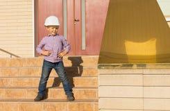 摆在台阶的盔甲的逗人喜爱的小孩 免版税图库摄影
