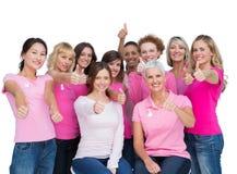 摆在和佩带乳腺癌的快乐的妇女桃红色 免版税库存图片