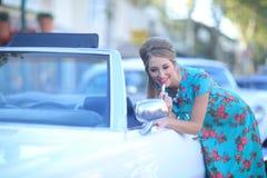 摆在和和在葡萄酒汽车附近的可爱的妇女 免版税库存照片