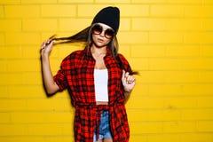 摆在和微笑在太阳镜的都市黄色墙壁背景,红色格子花呢上衣附近的美丽的年轻性感的行家女孩 免版税库存图片