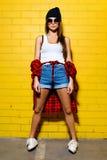 摆在和微笑在太阳镜的黄色墙壁背景,红色格子花呢上衣,短裤附近的美丽的年轻性感的女孩 免版税库存图片