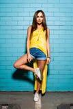 摆在和微笑在黄色礼服的都市蓝色墙壁背景,短裤,衬衣附近的美丽的年轻性感的行家女孩 图库摄影