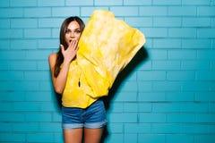 摆在和微笑在黄色礼服的都市蓝色墙壁背景,短裤,衬衣附近的美丽的年轻性感的行家女孩 免版税库存图片