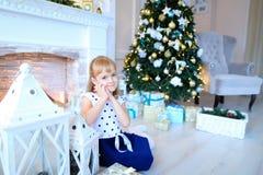 摆在和微笑对在白色新年的studi的照相机的逗人喜爱的女孩 图库摄影