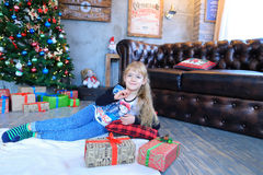 摆在和微笑对摄影师的照相机的女孩有礼物的 免版税图库摄影