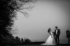 摆在和拥抱在老城堡附近的肉欲的愉快的夫妇在与一条美好的地平线的日落 免版税库存照片
