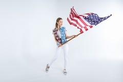 摆在和挥动美国旗子的年轻白种人妇女 免版税库存照片