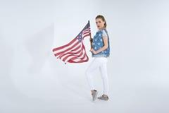 摆在和挥动美国旗子的年轻白种人妇女 免版税库存图片