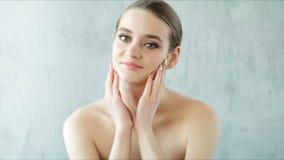 摆在和接触她的健康皮肤和光秃的肩膀的美丽的妇女 Skincare概念 股票视频