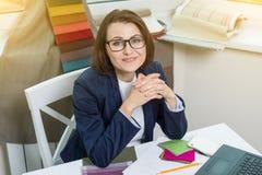摆在和看您的设计师或建筑师坐在办公室 免版税库存图片