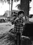 摆在和采取肩膀声学吉他的年轻人在公园 库存图片