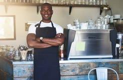摆在咖啡馆的微笑的黑人男性工作者 库存图片