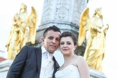 摆在喷泉前面的新婚佳偶 免版税库存照片