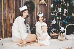摆在圣诞树前面的三个姐妹 库存图片