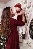摆在圣诞树旁边的美丽的家庭假日照片 免版税库存图片