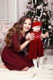摆在圣诞树旁边的美丽的家庭假日照片 图库摄影