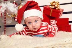 摆在圣诞树旁边的逗人喜爱的矮小的圣诞老人婴孩在有新年装饰的舒适家 图库摄影