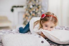 摆在圣诞树附近的一件白色毛线衣和蓝色牛仔裤的愉快的小女孩 免版税库存照片