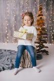 摆在圣诞树附近的一件白色毛线衣和蓝色牛仔裤的愉快的小女孩 库存照片