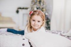 摆在圣诞树附近的一件白色毛线衣和蓝色牛仔裤的愉快的小女孩 库存图片