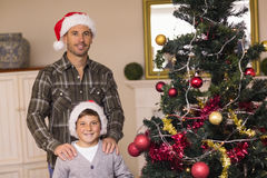 摆在圣诞树附近的爸爸和儿子 图库摄影