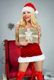 摆在圣诞老人服装的性感的美丽的白肤金发的妇女 库存照片