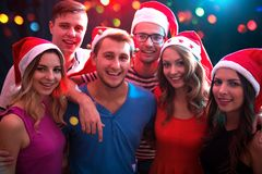 摆在圣诞老人的帽子的小组愉快的朋友 库存图片