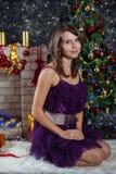 摆在圣诞节场面前面的少妇 免版税库存图片