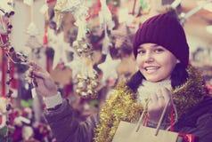 摆在圣诞节市场上的外套的十几岁的女孩 库存照片