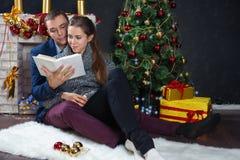 摆在圣诞节背景的年轻夫妇  免版税库存图片