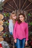摆在圣诞节装饰的两个美丽的女孩 免版税库存图片