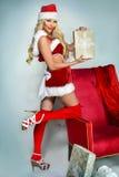 摆在圣诞节装饰附近的性感的年轻白肤金发的女孩 免版税库存照片