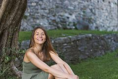 摆在在城堡的一棵树下的年轻女人 免版税库存图片