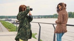 摆在在散步的石长凳的美丽的年轻女人在河在城市 影视素材