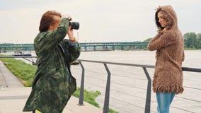 摆在在散步的石长凳的美丽的年轻女人在河在城市 股票视频